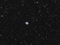 M57 The Ring Nebula in the constellation Lyra . The nebula is a shell of ionized gas given off by the central star during the final phases of its evolution prior to becoming a white dwarf. It lies approximately 2,300 light years from Earth. The smudge above and to the right of M57 is external galaxy IC 1296.